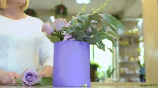 Florist with assistant make flower composition with roses inside box