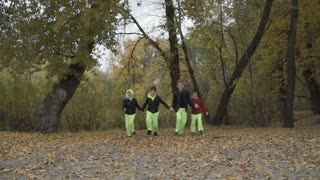 Four boys runs in autumn park on camera