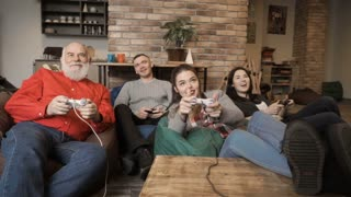 Four people relaxing at home and playing video game