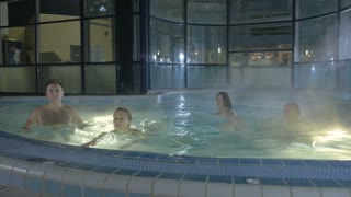 Four young people are swimming in the pool after sauna
