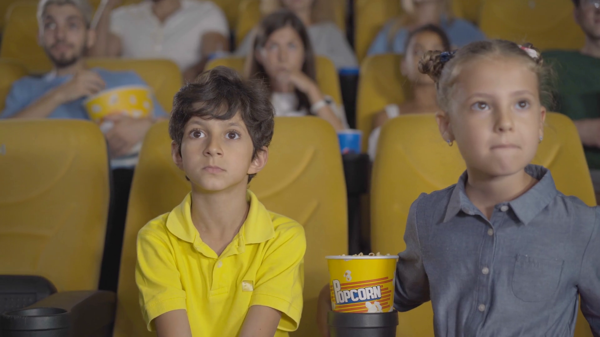 Frightened Middle Eastern Boy And Caucasian Girl Closing Eyes In Cinema Portrait Of Multiethnic Friends Watching Film In Movie Theatre Children Sitting On Yellow Chairs Looking At Horror Movie Stock Video Footage