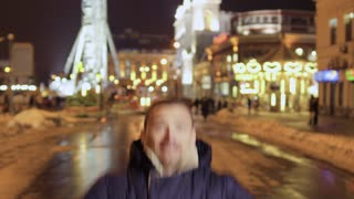 Funny adult man appears in front of camera at the blurred city background