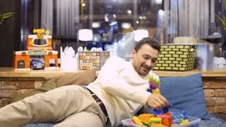 Funny adult man plays with kid constructor in children's room in cafe