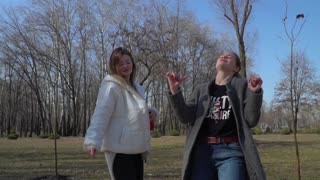 Funny girls dances to the beat of music and singing in the park