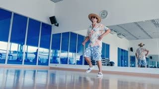 Funny man in sunglasses and hat dancing in gym
