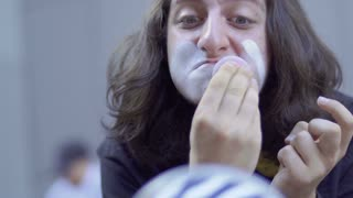 Funny mime applying white paint on his face