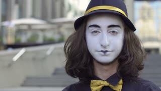 Funny mime in hat slap his cheek