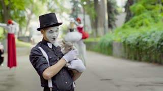 Funny mime joking with cat on the street