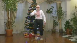 Funny old man dances near the Christmas tree