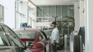 Funny swarthy guy dancing near the car in car showroom
