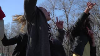 Funny teenagers dancing and singing in the park
