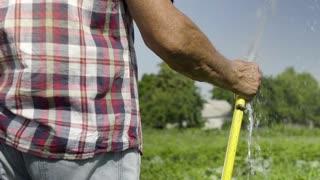 Gardener watering green meadow in slow motion using water hose