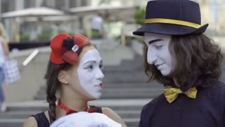 Girl and guy mimes play with hands