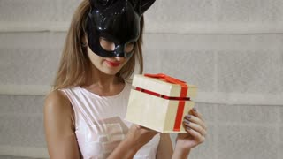 Girl in black mask open a gift box