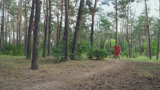 Girl in red dress with bow running cross forest