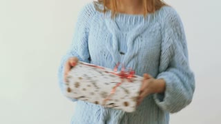 Girl in sweater dances with christmas present at white background