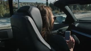 Girl is riding in the car in the passenger seat with phone