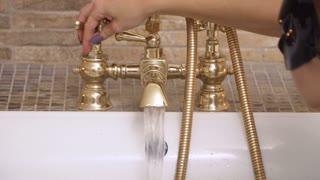 Girl open faucet in bathroom