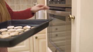 Girl put the baking tray with cookies in oven