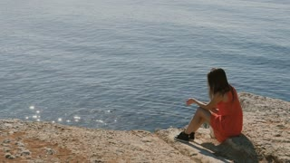 Girl sit on rock and throws stones into a blue sea
