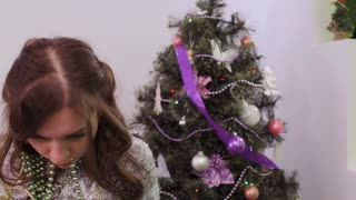Girl tired to decorate Christmas tree, garland in the mouth
