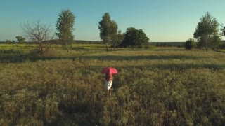 Girl with red umbrella walks at the field