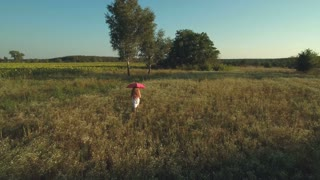 Girl with red umbrella walks in the meadow