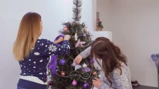 Girls decorate christmas tree