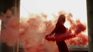 Gorgeous brunette dancing with red smoke at abandoned place