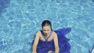Gorgeous model in blue dress swims in blue pool