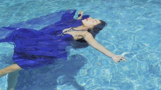 092491e052a52 Gorgeous fashion woman with dark hair in elegant yellow dress looking into  the camera while swimming in water of outdoor pool at night Stock Video  Footage ...