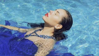 Gorgeous model in blue long dress with red lips swims in the pool