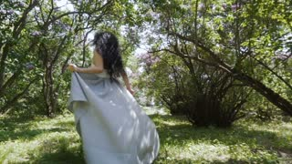 Gorgeous woman run through a garden in slow motion