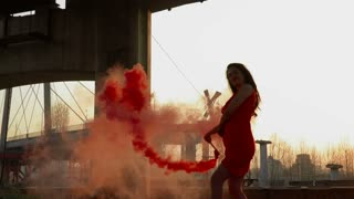 Gorgeous woman with red smoke flare dancing under abandoned bridge