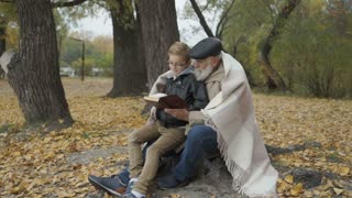 Grandfather and grandson read the book in autumn park