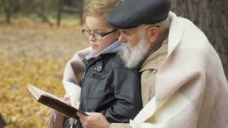 Grandfather with grandson read the book in autumn park