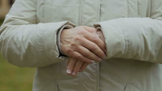 Grandmother rubs hands to warm up