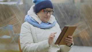 Grandmother with tablet relaxing outdoors