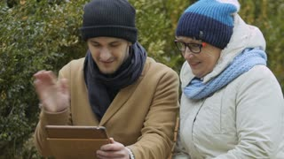 Grandson and grandma talks with relatives on video call at the tablet outdoors