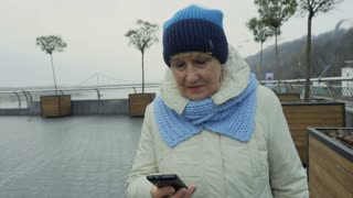 Granny uses phone walking outdoors