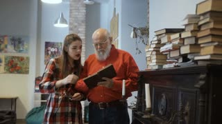 Gray-haired grandfather and granddaughter read interesting book together