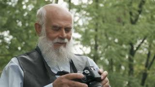 Gray-haired man photographs an autumn park