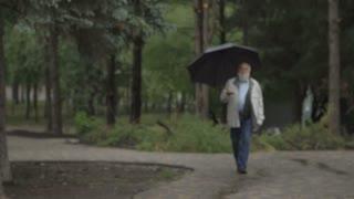 Gray-haired senior man walk with black umbrella in rainy park