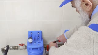 Gray-haired worker untwists nut on heating pipe