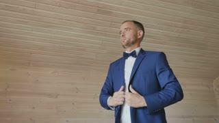 Groom straighten his jacket before wedding