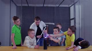 Group of boys explore Tesla coil in museum of popular science and technology