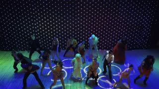 Group of crazy dancers with insane greasepaint are dancing on colorful stage