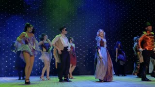 Group of fairytale heroes are dancing and singing on stage in theatre