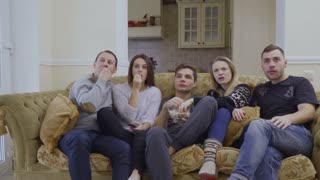 Group of friends watches movie at home and eat popcorn