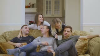 Group of young caucasian people relax on sofa at home and drinking coffee